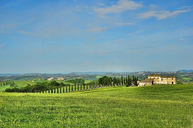 zelená krajina a v dáli stojící budova